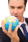Global business. Concept with a senior businessman holding mini globe stock photo