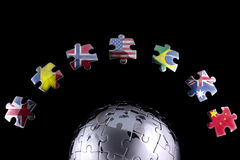 Global business concept. Jigsaw flags around a chrome globe stock photos