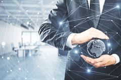 Global business concept. Businessman holding abstract polygonal network with globe on blurry office interior background. Global business concept. 3D Rendering Royalty Free Stock Image