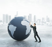 Global business concept. Businessman pushing abstract terrestrial globe on city background. Global business concept. 3D Rendering Stock Photography