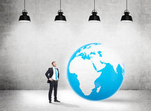 Global business. Concept with businessman standing in concrete interior with huge terrestrial globe and several ceiling lamps. Elements of this image furnished Stock Photography