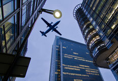 Global business. Concept - plane flying over office park with illuminated buildings in night scene Stock Photo