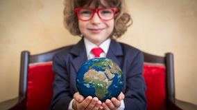 Global business concept. Portrait of young businessman kid in office. Global business concept. Elements of this image furnished by NASA Stock Photo