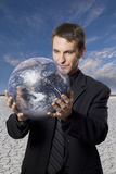 Global Business Concerns. Businessman holding an earth globe in the desert stock image
