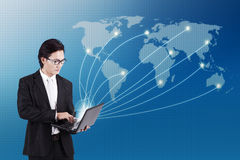 Global business connection. Businessman working on laptop computer over world map for social and internet connectivity concept Royalty Free Stock Photo