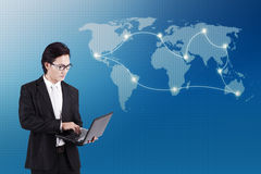 Global business connectivity concept. Businessman working on laptop computer standing in front of world map background and global business connectivity concept royalty free stock image