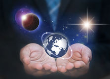 Global business. Business man holding the world in his hands surrounded by space and planets Stock Photography