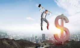 Global business and money concepts. Falling dollar currency. Jumping businessman crashing big dollar symbol with city view and sunlight on background. 3D royalty free stock images