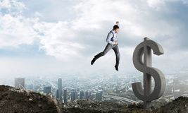 Global business and money concepts. Falling dollar currency. Jumping businessman in smart casual wear crashing big dollar symbol with city view on background stock photography
