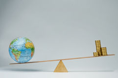 Global business. World globe and money coins stack balancing on a seesaw Royalty Free Stock Image