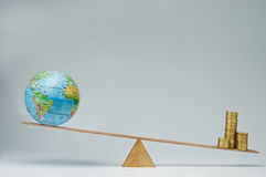 Global business. World globe and money coins stack balancing on a seesaw Royalty Free Stock Photography