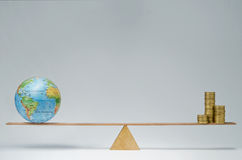Global business. World globe and money coins stack balancing on a seesaw Stock Photos