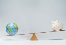 Global business. World globe and piggy bank balancing on a seesaw Stock Photos