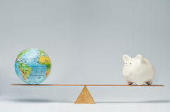 Global business. World globe and piggy bank balancing on a seesaw Royalty Free Stock Photography