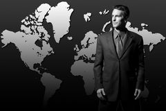 Global businessman World Domination. Businessman standing in front of world map facing america Stock Photo