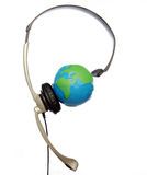 Global Call Center. Call center headset over a globe symbolizing a global call center support royalty free stock photo
