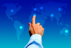 Global choices. Male hand touching a point on a world map, global choice concept Stock Photo