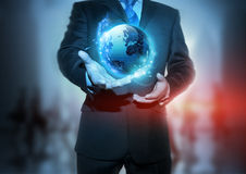 Global Communication. A businessman holding a glowing, connected, World Stock Images