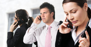 Global Communication. Businesspeople are calling on mobiles in front of an office building Royalty Free Stock Photo