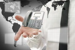 Global communication. Businessman in interactive space presenting telephone. Concept of global communication Royalty Free Stock Images
