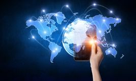 Global communication and networking. Close of businessman holding tablet pc and media world map on screen. Mixed media Stock Images