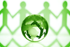 Global community. Paper chain men holding hands around a green globe concept for partnership, teamwork or global community stock photos