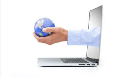 Global Computer Business Globalisation Business. A hand holding a world globe coming out of a laptop computer on a white background Royalty Free Stock Photo