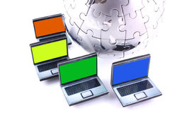 Global computer network. Laptops with one colour screens around a chrome jigsaw globe royalty free stock image