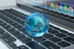 Global computer network communication, internet business and marketing concept. Blue transparent Earth globe on laptop keyboard macro view vector illustration