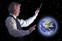 Global conductor. Business man trying to influence the blue planet stock image