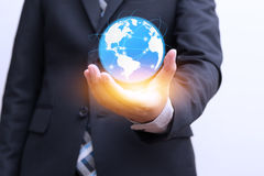 Global connection with digital planet in hand and orange light Royalty Free Stock Photo
