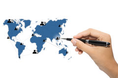 Global connectivity. Global map with people icons interconnected and hand holding pen on white background Royalty Free Stock Photography