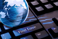 Global dating concept. Find love with black keyboard and glass globe above Stock Photo