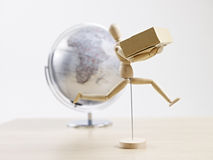 Global delivery. Wooden dummy carrying cardboard box with globe in the background, global logistics concept Royalty Free Stock Images