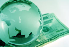Global economy. Close up of a new US $20 bill with glass globe Royalty Free Stock Photography