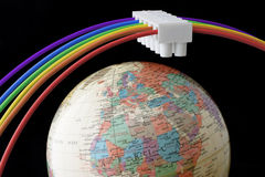 Global energy concept. Rainbow wire and  electric connector around globe as satellite Stock Images