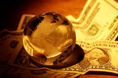 Global Finance. Glass Globe on Money With Creative Lighting.  Global Finance Concept