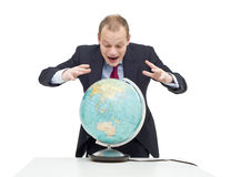 Global fortune. A businessman, hovering over a globe as if if looking at a fortune teller's sphere, seeing the possibilities and potential of emerging markets Royalty Free Stock Image