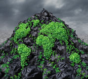 Global Garbage. Concept with a mountain of black plastic trash bags in a landfill background with a vine plant shaped as the planet earth growing through the Royalty Free Stock Photography