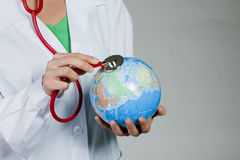 Global health. Female doctor listening to the Earth with stethoscope Stock Photography