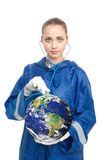 Global health problems. Doctor holding a globe and listen it with sthetoscope Royalty Free Stock Image