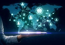 Global and hiring concept. Hand holding tablet with glowing social network map on dark background. Global and hiring concept royalty free stock image