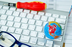 Global on keyboard with eyeglasses Royalty Free Stock Photo