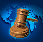 Global Law. And international business justice system with a judge gavel or mallet making a judgement based on government regulations with a world map in the Stock Photography