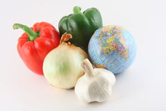Global Market. Red pepper, green pepper, onion, garlic and a globe of the world on a white background Stock Image
