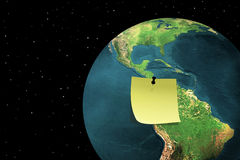 Global message. Sticky note on earth with black sky and stars Royalty Free Stock Images