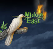 Global Middle East Crisis. With a white peace dove holding a burning olive branch on a stormy night sky as a concept of war and failed diplomacy in the persian Stock Image