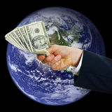 Global Money. Business man hand with money over the planet Stock Photos