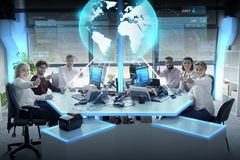 Happy business team with earth hologram at office Royalty Free Stock Images