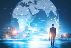 Global networking and business. Back view of businessman in night city looking at globe with network. Global networking and international business concept Stock Images